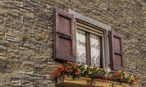 Traditionelles Haus mit alten Fenstern und Blumen und Fassade aus Andes Bronze