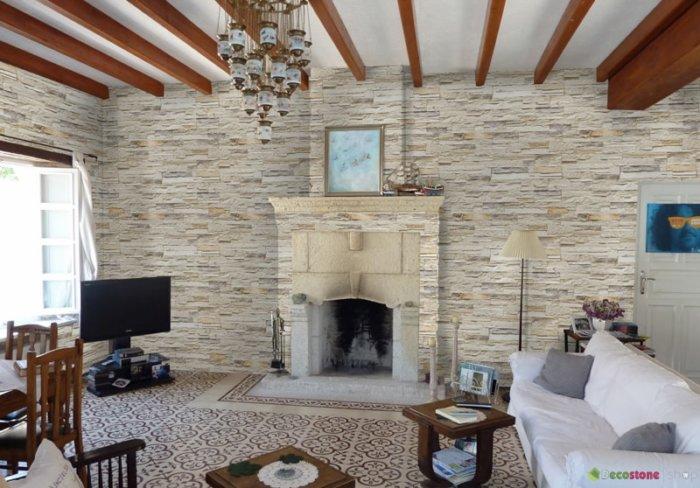 Schönes geräumiges Wohnzimmer mit imposantem Kamin und Steinwänden in hellen Tönen