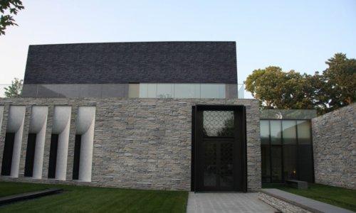 Modern Haus auf der Provinz mit Garten und Fassade aus künstlicher Stein im grauer tönen.
