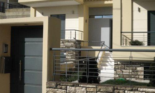 Eingang zum Familien Haus mit Vorgarten und dekorativen Kunststein in Olivenöl Nuancen
