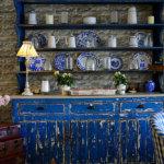 Alte blaue Küchenmöbel mit Geschirr und Glaswaren und alte Koffer im Laufe der Zeit mit dem Verzierungsstein Armorique Beige