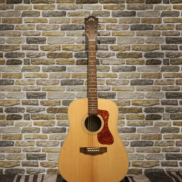 Eine klassische Gitarre vor der Wand, der aus dekorativem Stein Armorique beige verblendet ist.
