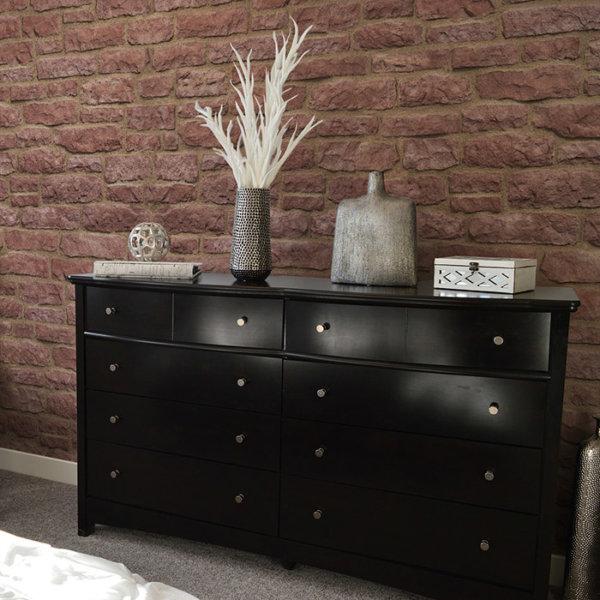 Schwarzer Nachttisch dekoriert mit silberne Accessoires und ein schwarzer Sessel im Schlaff Zimmer mit Wandverkleidung von Armorique Red