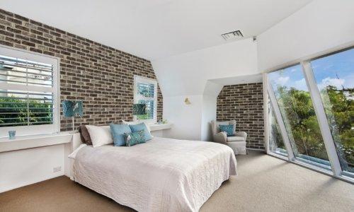 Weißes großes Schlafzimmer mit Sicht und Investitionsziegelstein an der Wand
