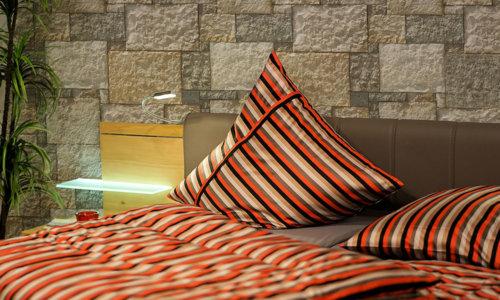 Bett mit farbigen, bunten Bezügen und dekorativem Stein in Beige tönen Nevada Beige