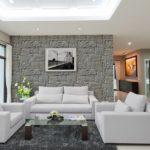 Helles Wohnzimmer mit weißen Sofas und Glastisch mit dem imposanten technischen Stein Nevada Gray.