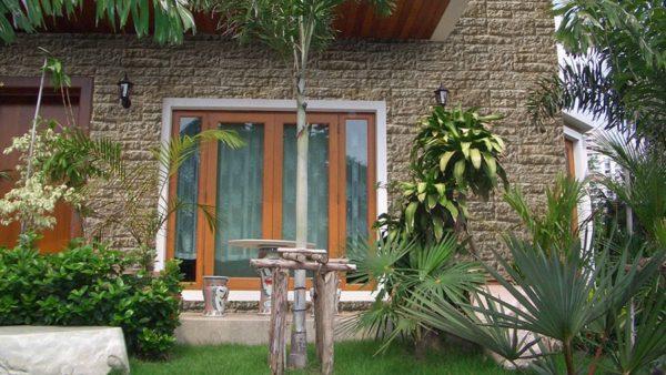 Fassade mit Vermont Beige in einem imposanten Haus und einem grünen Garten.