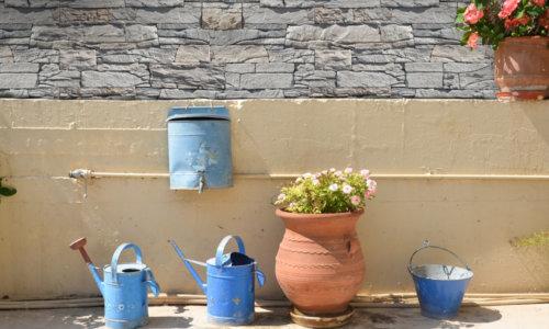 Klassischer mediterraner Innenhof mit blauer Gießkanne und Eimer in hellen Farben und in Grau den Investitionsstein Vivid Gray