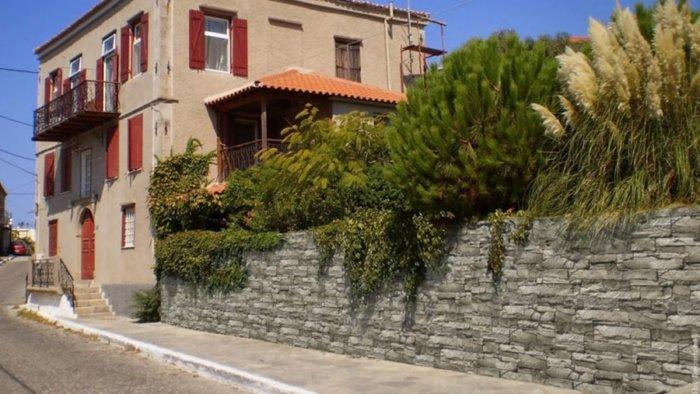 Typisches Haus in einem Dorf mit einem Innenhof und einem großen graue Mauer mit viel Grün