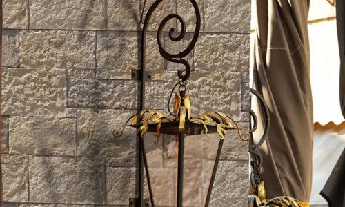 Eine Laterne mit vergoldeten Blättern, die an einem Verblender Stein Nevada Bronze befestigt ist.