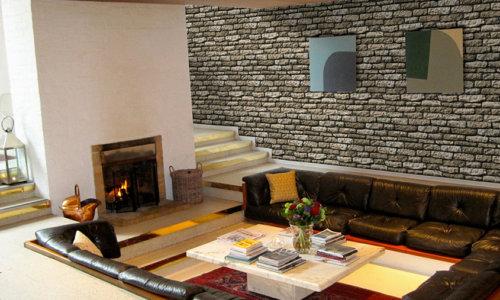 Riesige Couch mit Winkeln in einem riesigen Raum mit Kamin und an die große Wand verkleidet mit Vermont Olive Stein