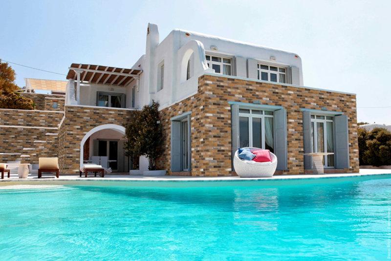 Villa auf einer kykladischen Insel mit Pool und teilweiser Fassade aus Investitionsziegeln.