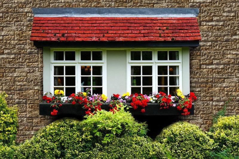 Hausfassade mit großen Fenstern verkleidet mit Decostone Vermont Gold