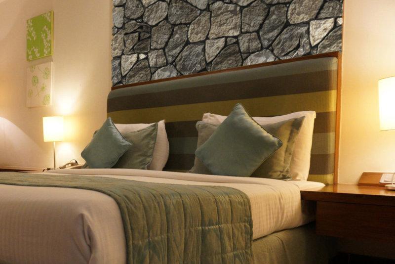 Großes, bequemes Doppelbett in einem Hotelzimmer und unregelmäßig künstlicher Stein über der Kopfstütze.