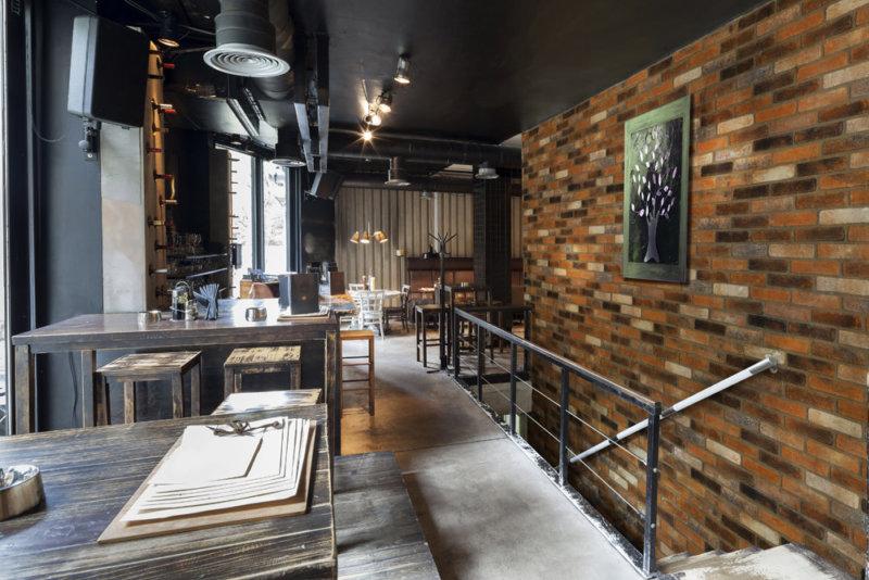 Modernes Bistro-Café mit großzügigen Räumen und zum Teil den Wänden sind mit Investitionsziegeln gebaut