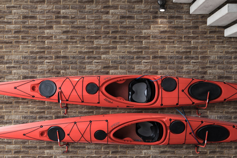 Wand mit braunem Ziegelstein ausgekleidet und Kanu aufgehängt