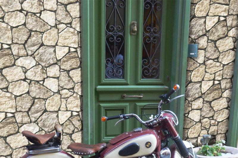 Ein altes Motorrad vor einem Haus mit einer grünen hölzernen alten Tür mit einer Steinfassade der unregelmäßigen, technischen Stein von Savoie Olive
