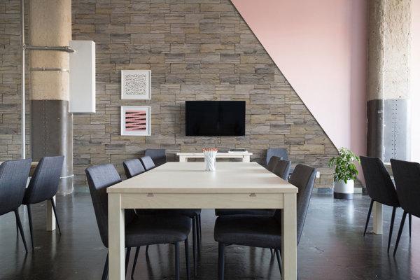 Geräumiger Raum mit Stein- und Farbwänden, ideal für Essbereiche.