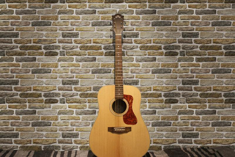 Eine klassische Gitarre an der Wand gelehnt, dekorativer Stein Armorique Beige