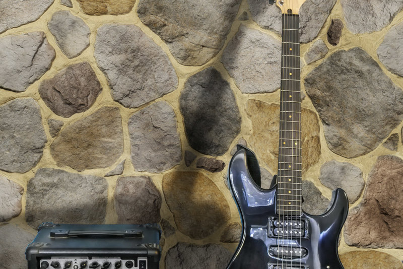 Die Gitarre mit ihrem Verstärker vor dem Mauerwerk von Decostone Savoie Beige