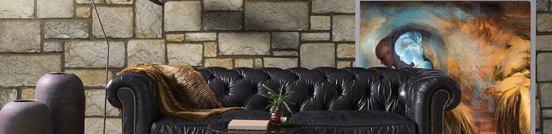 Modernes Wohnzimmer mit schwarzem Ledersofa und der Wandverkleidung ist mit unregelmäßigen Steinen aus der Reihe Chateau